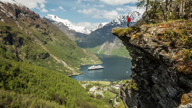 Norway, Geiranger, Geiranger fjord. Unesco World Heritage site. High Angle view on village and cruise ship MS Rotterdam of Holland-America line. Hiker