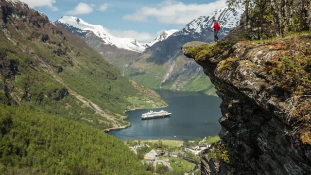 vídeos de stock e filmes b-roll de norway, geiranger, geiranger fjord. unesco world heritage site. person on cliff overlooking village and cruise ship ms rotterdam of holland-america line. hiker - embarcação comercial
