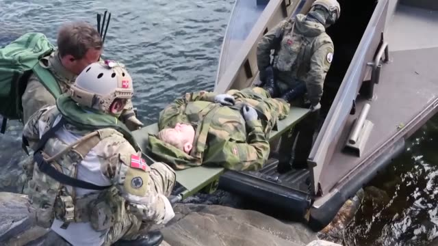 A Norwegian Coastal Ranger Commando administers an IV to a simulated casualty aboard a CB90class fast assault craft while conducting medical...