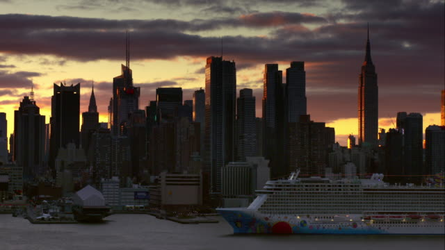 Norwegian cruise ship slowly moves along Hudson River in front of Midtown Manhattan skyline in the early morning hours.
