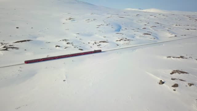 norwegian train passing in the middle of a snowy valley in nordland - rail transportation stock videos & royalty-free footage