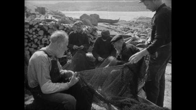 WS Norwegian waterfront rowboats EXT MS Norwegian men talking WS Sailboats in harbor VS Fishermen talking on shore cutting fishing nets