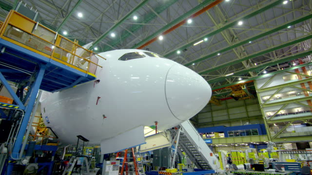 nose and body of plane in boeing hangar - etwas herstellen stock-videos und b-roll-filmmaterial