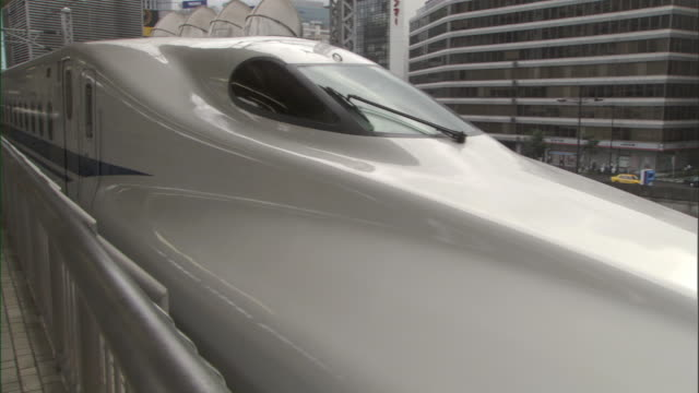 cu nose of streamlined first car of bullet train shinkansen slowly departing station / tokyo, tokyo prefecture, japan - train vehicle stock-videos und b-roll-filmmaterial