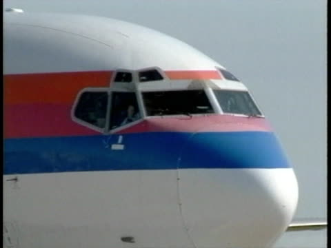 nose of white airplane w/ red & blue stripe coloring design, possibly passenger class, taxiing, unidentifiable male pilots in cockpit window waving... - white点の映像素材/bロール
