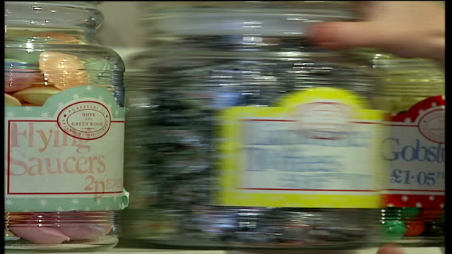 nostalgia for old fashioned sweet shops liquorice toffees in glass jar on shelf jar of pear drops being taken from shelf - pear stock videos & royalty-free footage