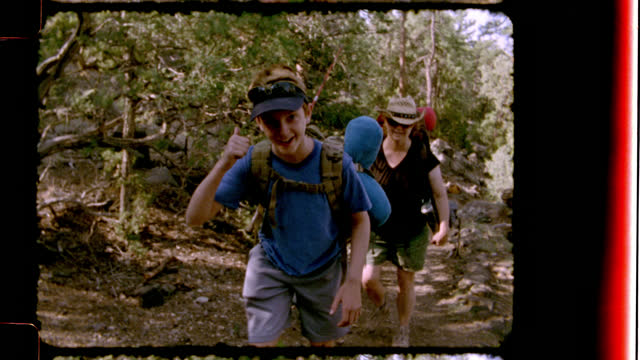 nostalgic family film footage of mother and kids hiking on rugged trail smiling and waving at camera as they pass. - bruder stock-videos und b-roll-filmmaterial