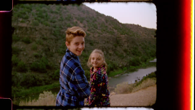 nostalgic film footage of brother and sister in bath robes looking out over the rio grande river and smiling at camera on family camping trip to black rock hot springs. - di archivio video stock e b–roll