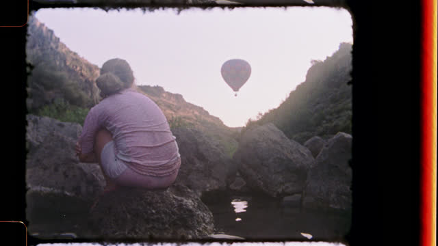 vidéos et rushes de nostalgic film footage of daydreaming young girl looking up at hot air balloon from rocky perch at black rock hot springs. - rêvasser