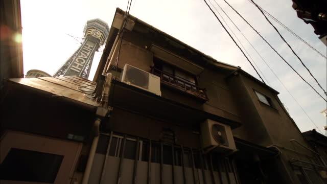 nostalgic townscape with tsutenkaku tower, osaka, japan - 老朽化点の映像素材/bロール