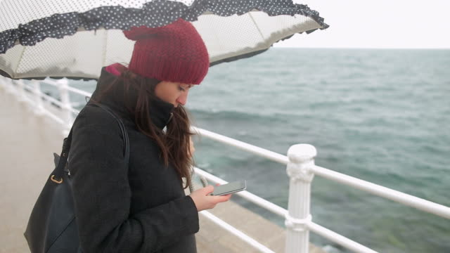 nostalgic young woman browsing her smartphone. - umbrella stock videos and b-roll footage