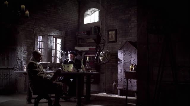 Nostradamus dictates his studies to a scribe.