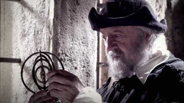 nostradamus examines a gyroscope near a window. - historische kleidung traditionelle kleidung stock-videos und b-roll-filmmaterial
