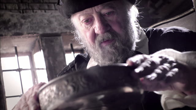 nostradamus examines the contents of a chalice on a table. - fortune telling stock videos and b-roll footage