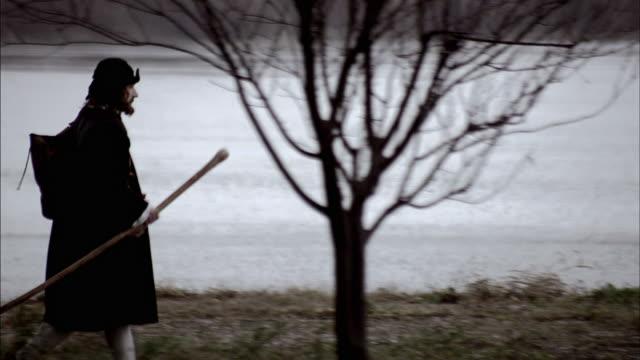 nostradamus follows a path to a lake's shore. - solo uomini maturi video stock e b–roll