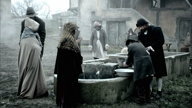 nostradamus oversees a villager washing his hands in a basin at a well. - periodo medievale video stock e b–roll