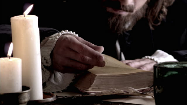 nostradamus reads a book by candlelight. - historical reenactment stock-videos und b-roll-filmmaterial