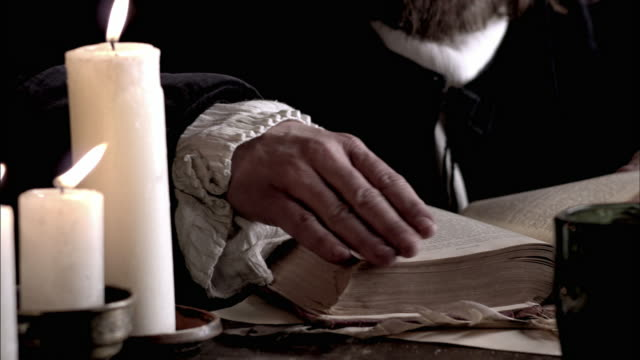 Nostradamus reads a book by the light of a candle.