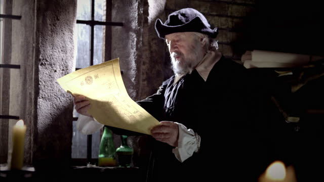 nostradamus reads a parchment by a window, then crosses the room to a globe. - historische kleidung traditionelle kleidung stock-videos und b-roll-filmmaterial