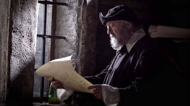 nostradamus reads a piece of parchment by the light of a window as a candle on a table snuffs out in a breeze. - weiser mann stock-videos und b-roll-filmmaterial