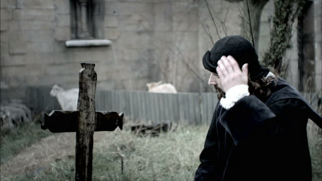 nostradamus removes his hat and crosses himself in front of a tombstone in a cemetery. - historical reenactment stock videos & royalty-free footage