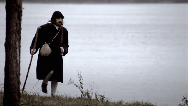nostradamus walks along a lake shore. - solo uomini maturi video stock e b–roll