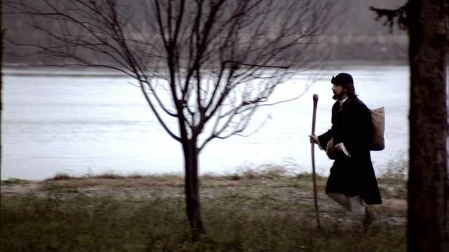 nostradamus walks along a path next to a lake. - solo uomini maturi video stock e b–roll