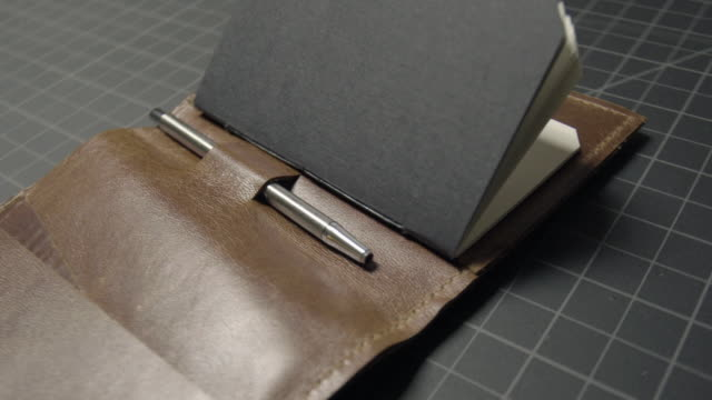notebook and pen from a vintage leather wallet. - leather stock videos and b-roll footage