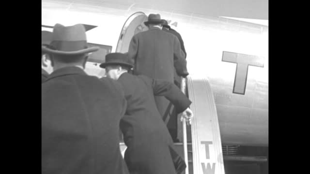 vs noted businessman sir victor sassoon and men clustered around the passenger door of a lindbergh line twa propeller airplane / inside the cabin a... - twa video stock e b–roll