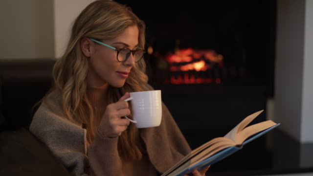 vídeos de stock e filmes b-roll de nothing beats a cozy weekend in with a good book - café bebida