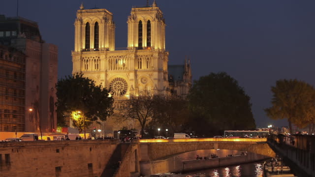 ws td notre dame cathedral and river seine illuminated at night / paris, ile de france, france - notre dame de paris stock videos & royalty-free footage