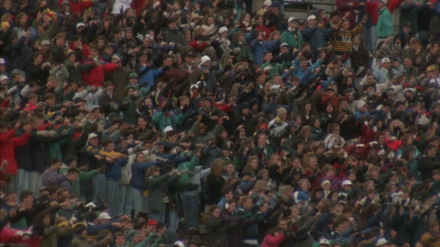 Notre Dame football fans move their arms back and forth in unison.