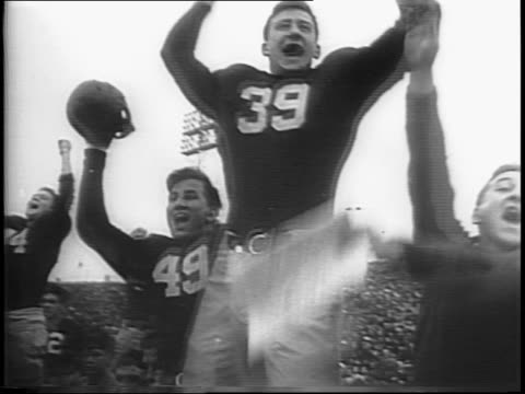 vídeos de stock e filmes b-roll de notre dame players cheer and run to the sideline / notre dame quarterback frank dancewicz passes to william o'connor on the 3 yard line / robert... - umbigo