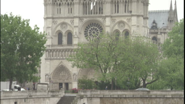 notre dame sits above traffic passing over the pont neuf and seine river in paris. - ポンヌフ点の映像素材/bロール