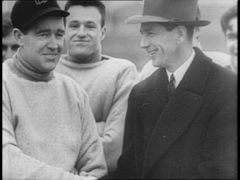notre dame students gather and cheer to welcome new football coach frank leahy / leahy in coat and hat smiles at crowd / football players run during... - anno 1941 video stock e b–roll