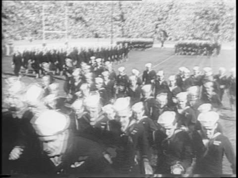notre dame vs tulane / sailors parade on field run into stands / game starts highlights include notre dame drive and touchdown / full stadium... - anno 1944 video stock e b–roll