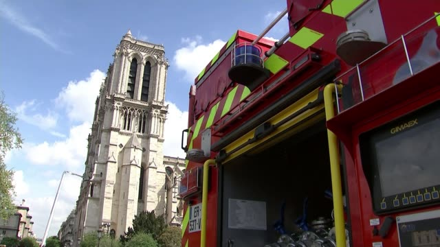 800m Euros pledged to rebuild NotreDame FRANCE Paris Notre Dame Cathedral with fire engine in foreground Firefighters towards Firefighters on...