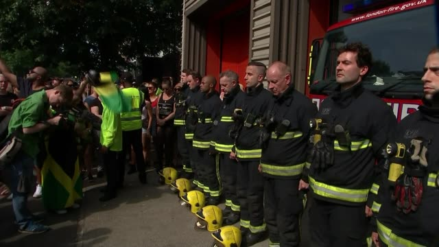 Silence observed for victims of Grenfell Tower fire ENGLAND London Notting Hill EXT Firefighter helmets lying on ground Firefighters observing...