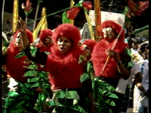 vídeos de stock e filmes b-roll de notting hill carnival aftermath ms people in costumes dancing around b/g float people watching ms people in red fluffy costumes towards dancing ms... - notting hill