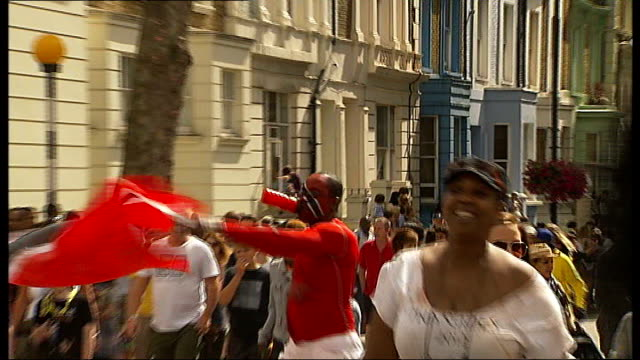 notting hill carnival begins; **music heard sot** man waving trinidad and tobago flag and with face painted in flag colours people in parade towards... - itv london tonight weekend stock videos & royalty-free footage