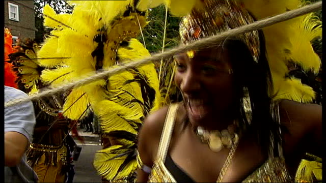 london notting hill ext carnival participants dancing to drums during parade man playing steel drum sot jerk chicken cooking on barbecue high shot... - headdress stock videos & royalty-free footage