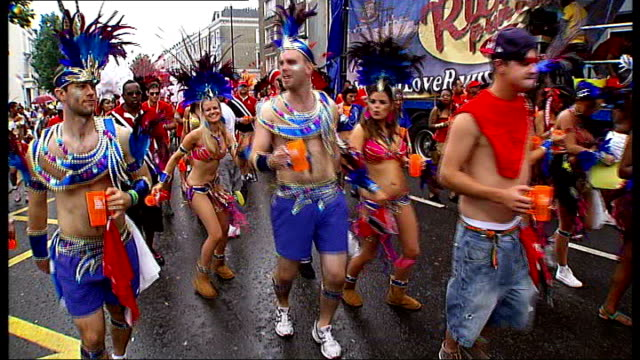 london notting hill ext **music heard sot** dancers towards in carnival parade vox pops performers along and dancing two men watching from window... - headdress stock videos & royalty-free footage