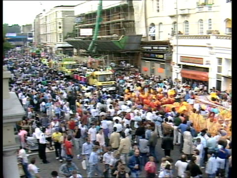 vídeos de stock e filmes b-roll de preparations itn lib england london notting hill crowds line street as parade along lr tms people in bright feathered costumes dancing as crowds look... - notting hill