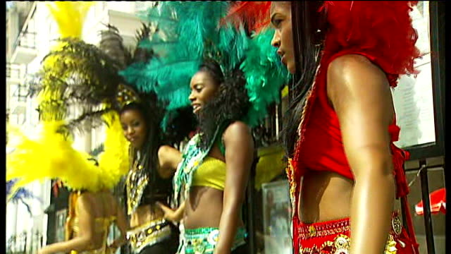 notting hill carnival preparations woman in peacock feathers smiling next to woman in black feathers close shot of steel drums played women wearing... - headdress stock videos and b-roll footage