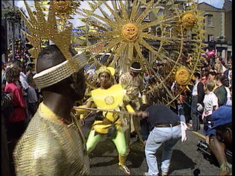 vídeos de stock e filmes b-roll de notting hill carnival sf england london notting hill tgv carnival march in progress pull out black men and women in glittering costumes ms dancers in... - notting hill