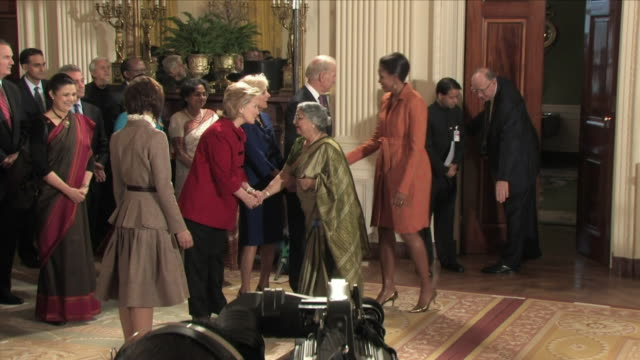 stockvideo's en b-roll-footage met nov 2009 michelle obama and gursharan kaur, wife of prime minister of india, entering east room / white house, washington d.c., usa / audio - 2009