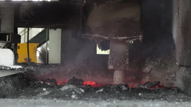 A Novelis Inc employee sweeps scraps of aluminum beside the melting furnaces at the company production facility in Yeongju A forklift moves decoated...
