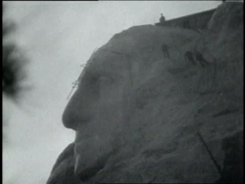 vídeos de stock e filmes b-roll de november 09 1931 montage men suspended on mountain face carving the head of george washington / mount rushmore keystone south dakota united states - 1931
