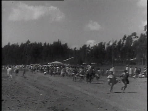 stockvideo's en b-roll-footage met november 11, 1935 montage natives riding down road road on horseback, and running with rifles / addis ababa, ethiopia - 1935