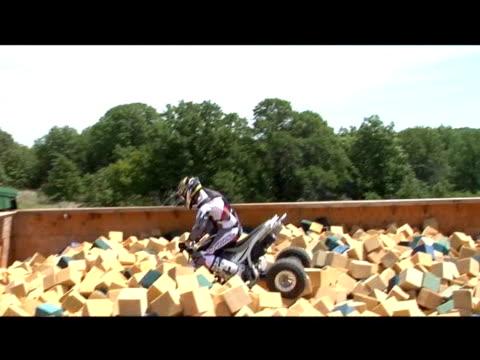 vidéos et rushes de november 14, 2006 montage a professional all terrain vehicle rider taking a practice run into a foam pit - format vignette